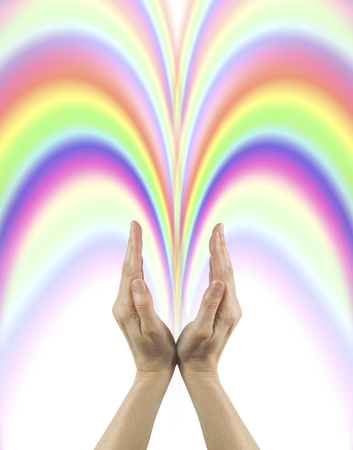 channeling: What you give out comes back ten fold - female color healer with hands cupped in v shape sending out rainbow colored healing energy Stock Photo