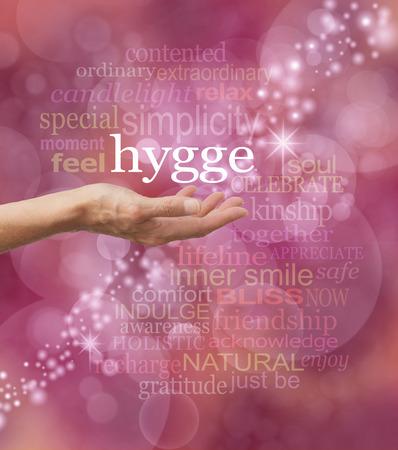 HYGGE トレンド - 警告赤ボケ背景に関連する単語の雲に囲まれた上に浮いて HYGGE デンマーク言葉が流行りと伸ばした女性の手を共有します。