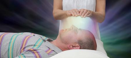Channelling Healing Energy - female with hands held six inches above a male patients face displaying coloured light on a dark background