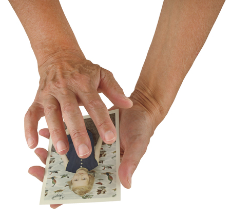 energy healing: Sending healing energy via connecting with photo - a pair of female hands holding a photo of a young girl, sending distant healing isolated on a white background