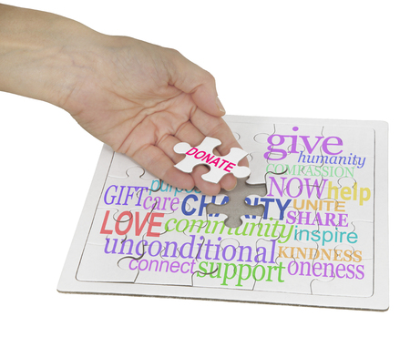 humility: Donate to Charity Puzzle  - hand holding a jigsaw puzzle piece showing the word DONATE, the remainder of the puzzle contains a charity word cloud on white background