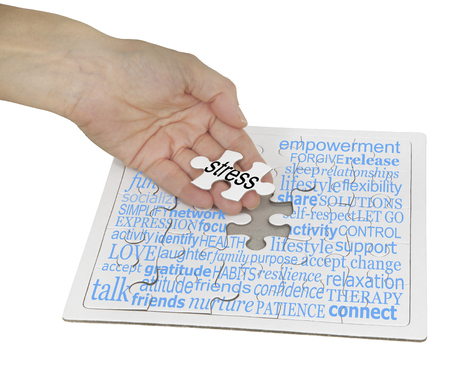 Stress Management Puzzle Word Cloud -  a hand holding the final jigsaw piece over a jigsaw puzzle  showing a word cloud containing words relevant to stress management Stock Photo
