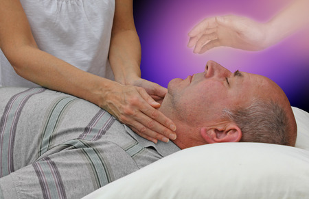 Spiritual help during a healing session - female hands laid either side of a male patient's throat channeling energy together with the help of a higher power on a dark purple background photo