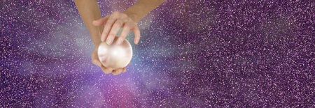 Fortune Teller holding crystal ball on sparkling banner - Female fortune teller holding a large  crystal ball in cupped hands against a sparkling magenta  background with copy space Foto de archivo