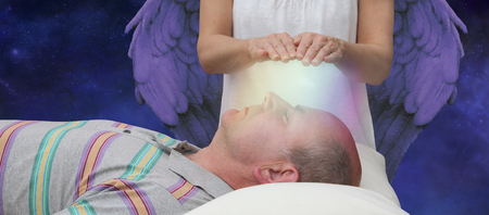 Angelic help during a healing session - female hands hoovering above a male patient's face channeling energy together with a higher power in the background depicting Angelic help photo