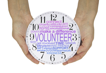 The Time to Volunteer is NOW - female hands holding a no hands clock face with a VOLUNTEER word cloud isolated on a white background