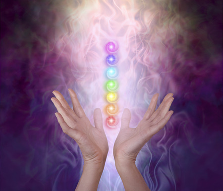 Working with the Seven Major Chakra Energy Vortexes  -  female healers hands either side of seven chakra vortexes on an ethereal dark to light misty swirling energy field