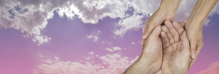 Caring in the Community Charity banner -  wide banner with a womans hands holding a mans cupped hands in a needy gesture on a beautiful pink and blue sky background  with copy space on the left