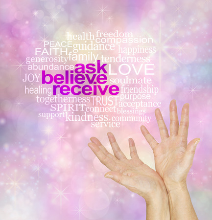 Ask and it is Given - pink and blue  sparkling bokeh background with white words ASK BELIEVE RECEIVE surrounded by a relevant word cloud and open hands beneath reaching up Stock Photo