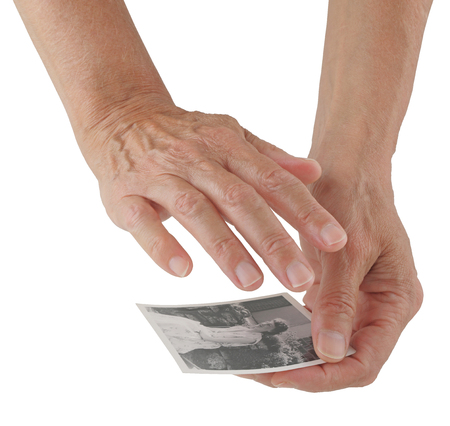 Psychic connecting to deceased using photo - female hands holding black and white photo of deceased woman isolated on a white background Stock Photo