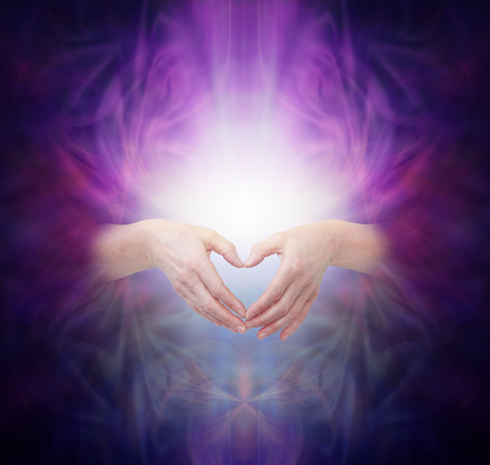 Sacred Healing Energy - female hands  emerging from a deep purple background making a heart shape over a bright glowing energy manifestation with plenty of copy space