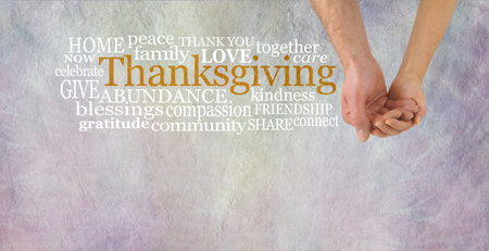 Celebrate Thanksgiving Together - Male hand cupped by female hand beside a THANKSGIVING word cloud  on a grey stone effect background with copy space below Banco de Imagens