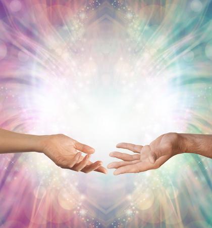 Männliche und weibliche Energie - eine weibliche Hand und eine männliche Hand mit den offenen Palmen, die sich gegen einen schönen verwickelten männlichen und weiblichen farbigen Energiehintergrund mit Kopienraum oben gegenüberstellen