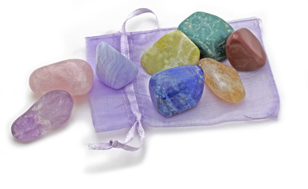 Organza Pouch with Chakra Crystal Set   -  Chakra Crystal Set of eight rainbow colored stones placed on a lilac organza pouch on a white background Stock Photo