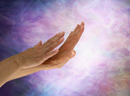 Sensing the light - female lightworker with hands positioned out of appearing out of darkness sensing the energy field depicted by white light and wispy pink gaseous formations