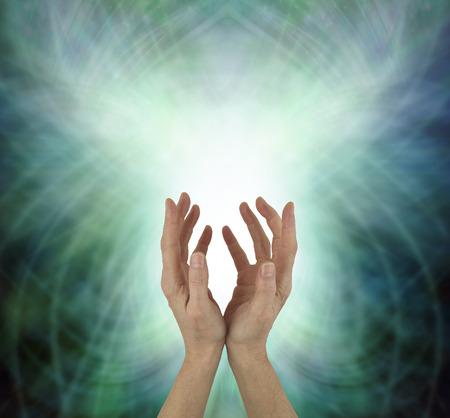 Emitiendo energía de sanación de chakra del corazón hermoso: manos femeninas que alcanzan hacia arriba enviando energía del corazón contra un fondo verde de formación de matriz de energía con espacio de copia