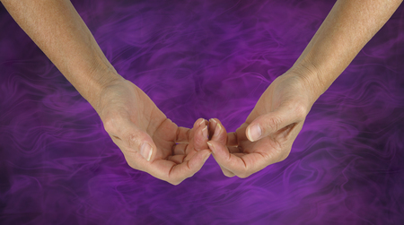 The Humble Healer -  female hands with the back of the fingers touching in a gentle gesture of hope isolated on a purple energy formation background