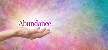 Attract Abundance - female open palm hand with a deep pink ABUNDANCE floating above on a pink and blue rustic stone background with copy space Stock Photo