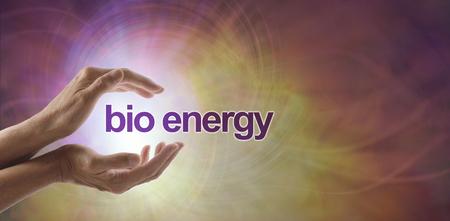 Bio-energie - nog een andere naam voor genezing - vrouwelijke holle handen met de woorden BIO ENERGY drijvend tussen een witte, roze en oranje vortex energievormingsachtergrond