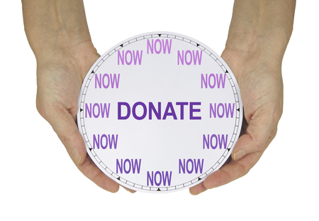 Please make a donation NOW  - female hands holding a clock with no hands that has NOW in place of the numerals and DONATE instead of hands isolated on a white background