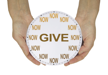 Please GIVE what you can NOW  - female hands holding a clock with no hands that has NOW in place of the numerals and GIVE instead of hands isolated on a white background