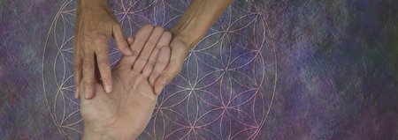 Your Palms are a map of your past and future life - female palm reader holding a male hand examining the lines and bumps against a flower of life rustic stone background