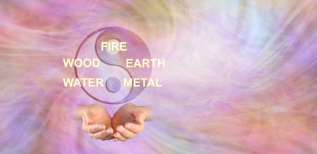 De 5 elementen van de traditionele Chinese geneeskunde - yin yang symbool boven een paar holle handen en de woorden BRAND HOUT AARDE WATER METAAL tegen een etherische energieachtergrond