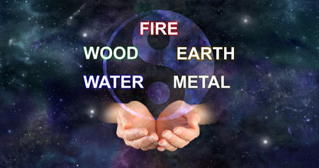 The Five Elements of Traditional Chinese Medicine -  yin yang symbol above a pair of cupped hands and the words FIRE WOOD EARTH WATER METAL against a deep space background