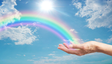 female hand with a bright rainbow arcing across a blue sky with fluffy clouds and a bright sun burst Stockfoto