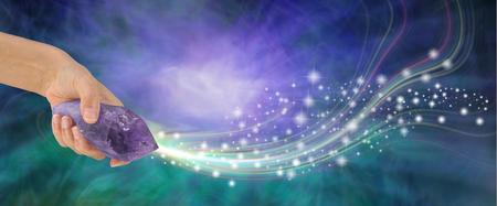 Masywny ametyst z piękną energią - kobieca ręka trzymająca dużą zakończoną ametystową różdżkę kwarcową wystrzeliwującą iskierki na fioletowym i jadeitowym tle energii z przestrzenią do kopiowania Zdjęcie Seryjne