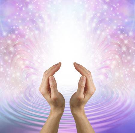 Focus your mind on sending pure healing love - female hands in cupped position against a beautiful feminine shimmering sparkle and water ripple background depicting unconditional love