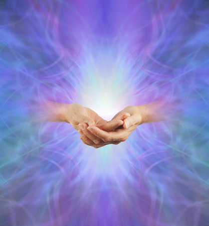 Sacred Purple Ray Healing Energy - female hands  emerging from a purple energy background making cupped hands gesture with a bright light behind and plenty of copy space Stock Photo