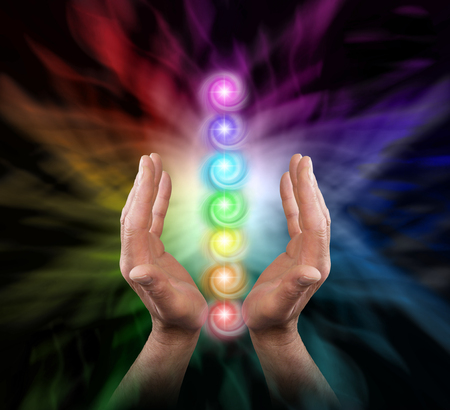 Sending Chakra Healing Energy - Male parallel hands facing upwards against a multicoloured background of energy and the Seven Chakras floating between his hands