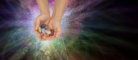 Crystal Healer Offering Chakra Crystals - female therapist holding a set of chakra crystals against a radiating multi-coloured paua shell mosaic background with copy space Stock Photo