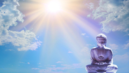 Take time out to enjoy the beauty of Nature - Buddha in Lotus Position against beautiful golden sun beaming down and blue sky with copy space