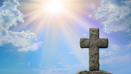 Symoblic Cross of Jesus Christ and Gods Light - Rugged stone cross in foreground with a bright blue sky and stuffing sun burst shining down providing copy space on the left