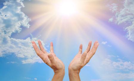 Encabezado del sitio web de curación: las manos del curandero extendidas que se extienden hacia un resplandor solar radiante con cielo azul y nubes esponjosas Foto de archivo
