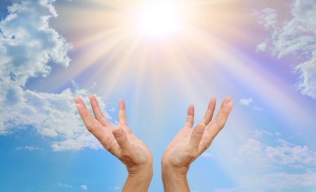 Healing website header - healer's hands outstretched reaching up towards a bright sunburst beaming down with blue sky and fluffy clouds Stockfoto