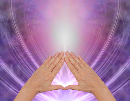 Working with Pyramid Healing Energy - female hands making a triangle shape on a magenta purple flowing triangular shaped energy field with plenty of copy space above