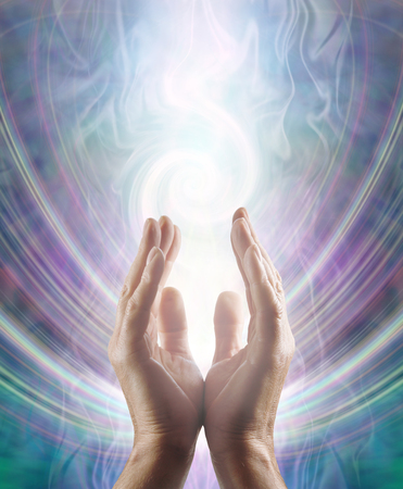 Sensing Spiralling Healing Energy - male  hands reaching up and sensing an ethereal spiralling white light flowing energy form with copy space
