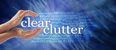 Make space in your life and clear your clutter - female cupped hands around the words CLEAR CLUTTER surrounded by a relevant tag word cloud on a dark ethereal wispy feather background Reklamní fotografie - 99707467