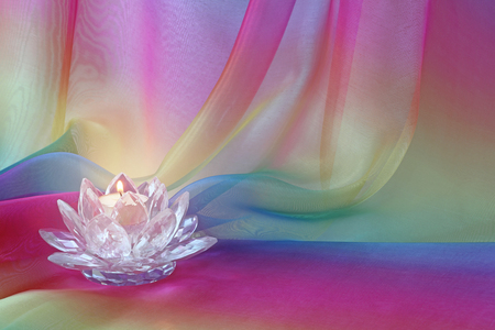 Lotus Light rainbow chiffon background - a lotus flower shaped cut glass candle holder with a lit candle, against rainbow coloured draped flowing chiffon material