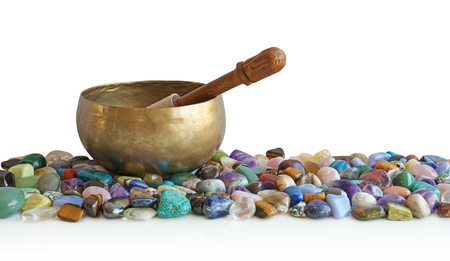 Singing bowl resting on bed of tumbled healing stones - a tibetan singing bowl atop a neat selection of multicoloured healing chakra stones against a white background