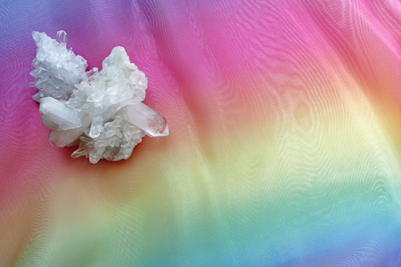 Crystal healers Memo Background - large complex quartz cluster in top left corner against a graduated rainbow coloured chiffon surface ideal for a message Stock Photo