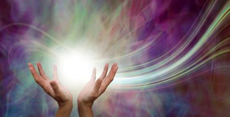Impresionante fenómeno de energía curativa: manos femeninas que alcanzan una bola de energía blanca con un rastro de láser y un fondo de campo de energía etérea verde rosa