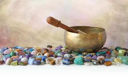 Tibetan Singing Bowl surrounded by tumbled healing stones - brass tibetan singing bowl with mallet  against a smokey effect background sitting on a selection of tumbled healing stones