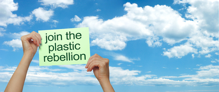 Join the plastic rebellion against life threatening waste - female hands holding up a green placard saying  JOIN THE PLASTIC REBELLION against a wide blue sky and cloud plus copy space