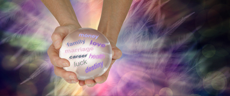 The crystal ball can reveal many things about your future - hands holding a large clear crystal ball showing various words on an ethereal multicoloured feather background with copy space Banco de Imagens