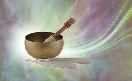 Geluidstherapie-instrumenten en hun prachtige energieveld - Tibetaanse klankschaal met hamer naast stemvorken tegen een stromende energieachtergrond