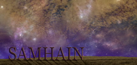 Celebrate Samhain summers end background - warm coloured starry cloudy autumnal night sky background with a simple grassy hilltop and the word SAMHAIN  and copy space above Stock Photo